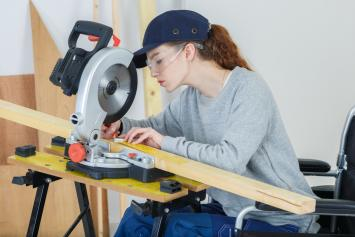 Young woman in wheelchair at drafting table